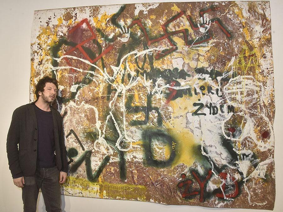 Le peintre Orsten Groom pose avec son travail plein de creepy tags durant Aérosolthérapie