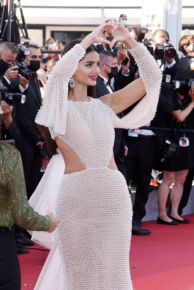 """Cette jolie modèle de blanc vêtue sait faire le """"Aline I love you"""" avec ses doigts de profil !"""