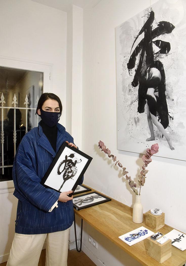 Galerie Ephemere Expo Deyi X Chris Calvet La Styliste Adriana Gagigas de Deyi pose devant des calligraphies de Chris Calvet