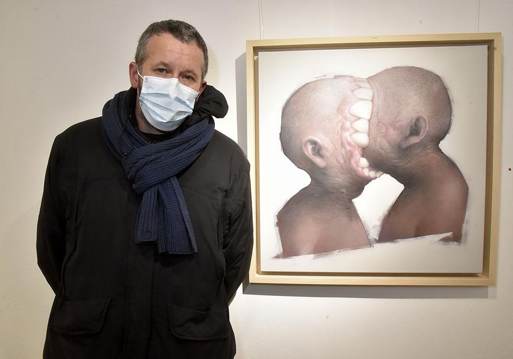 Bom.K pose avec un portrait decannibales durant pendant Ma Thématiques Expo Bom.K à la Galerie Joël Knafo
